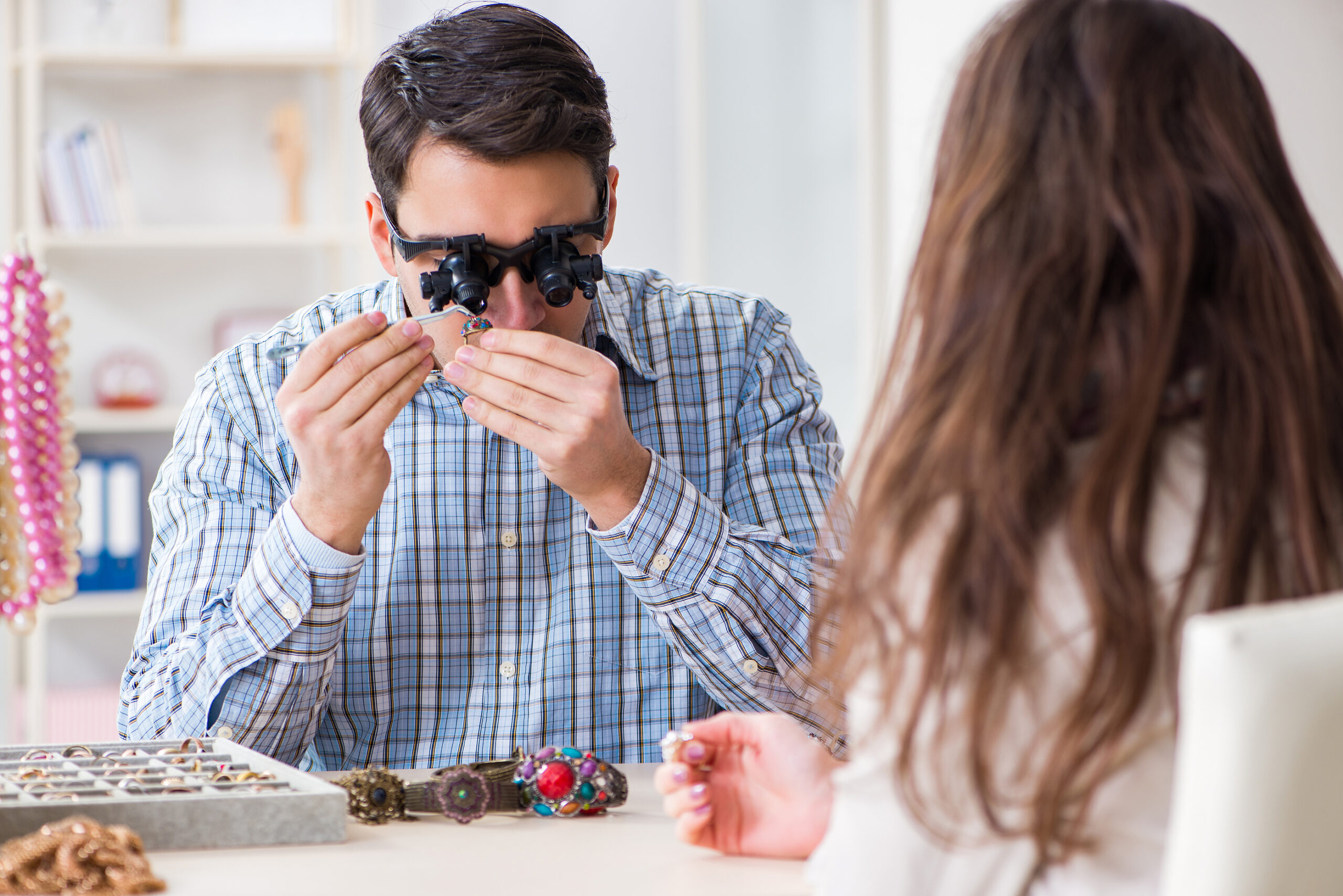 Woman visiting jeweler for jewelry evaluation